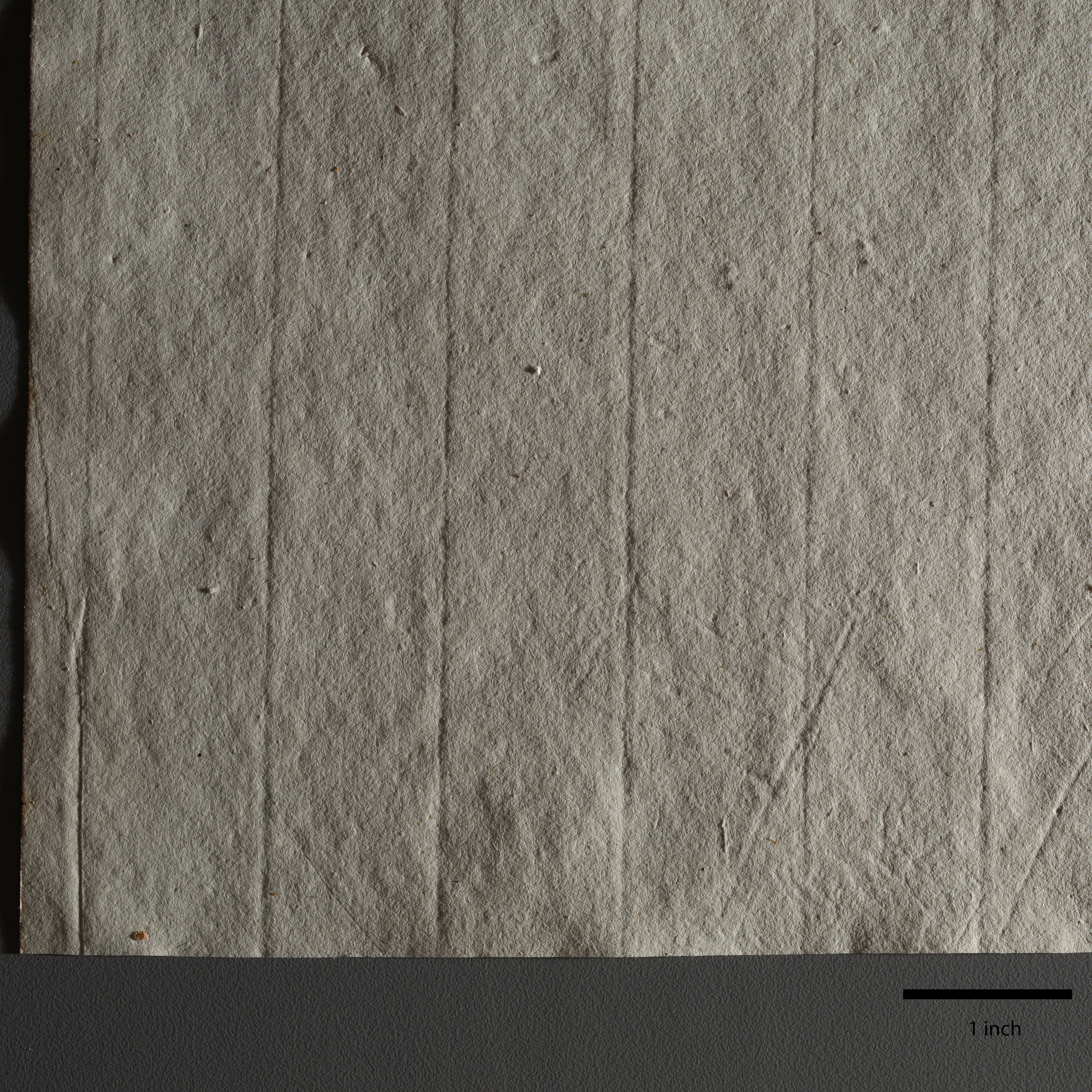 This photograph shows a piece of paper very close up, with a soft, uneven texture and regular vertical lines, suggesting indentations. It is resting on a gray surface. Below the paper to the right is a thick black line marking one inch.