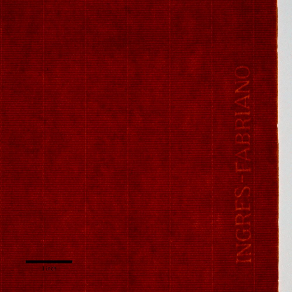 """A dark red paper is structured by a regular grid pattern. Close to its right edge, watermark letters spell out """"Ingres-Fabriano."""" A thick black line marks one inch at bottom left."""