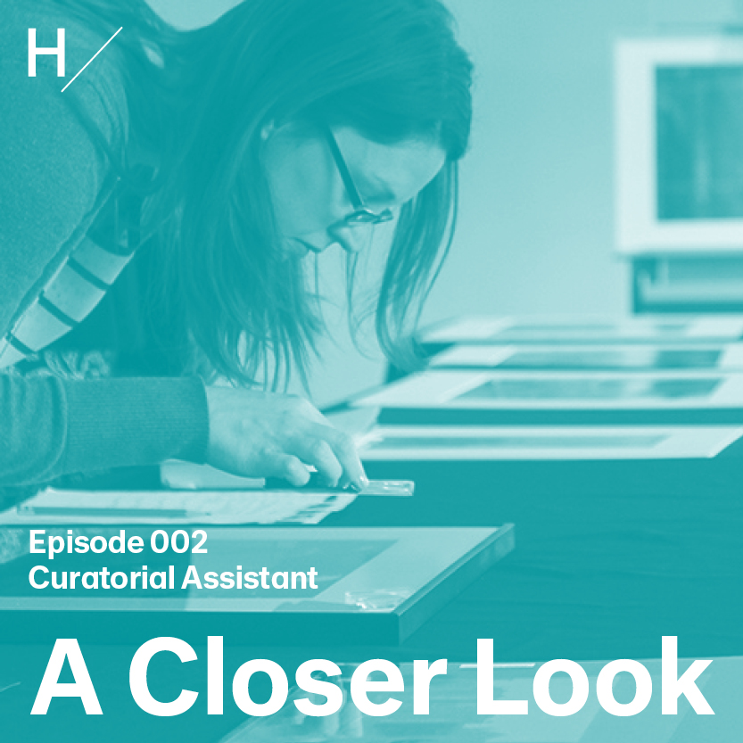 """Heather Linton is bent forward over a table, closely looking at framed artworks laid out in front of her. She wears glasses and her dark hair falls forward and frames her face. There's a blue overlay on the image with white text that reads """"Episode 002,"""" """"Curatorial Assistant,"""" and """"A Closer Look."""""""