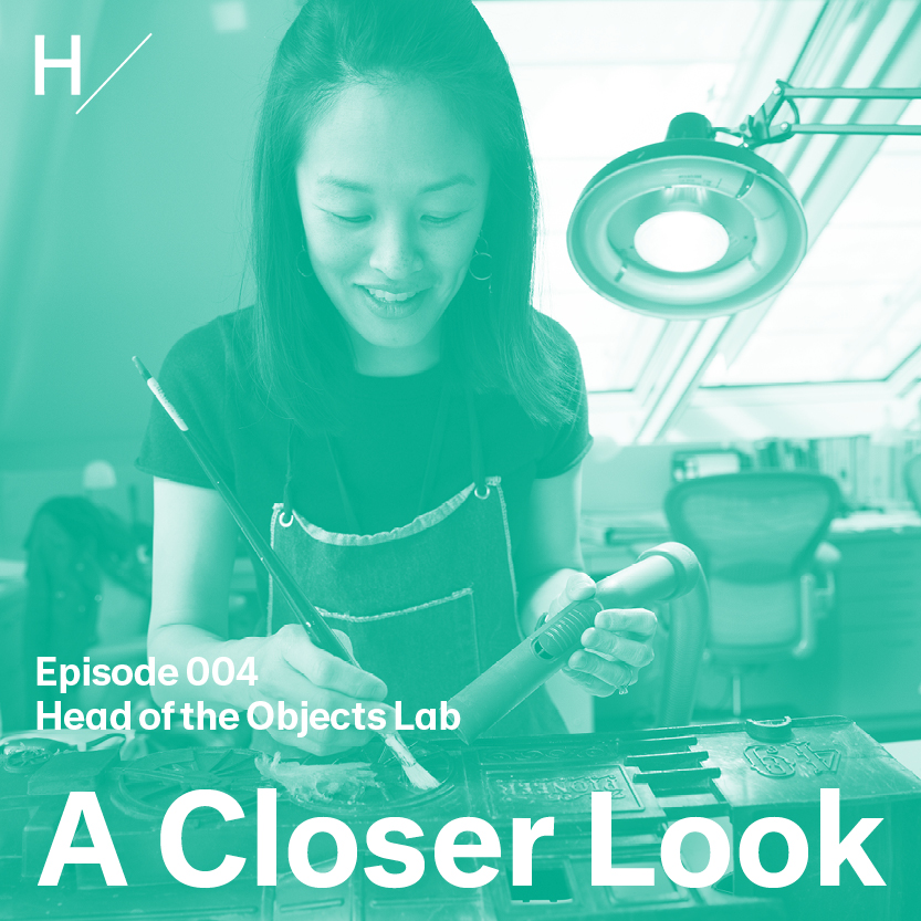 """Angela Chang is bent slightly forward over a three-dimensional artwork on a table in front of her. She has dark, shoulder-length hair and is smiling. She is wearing a work apron over a dark short-sleeved t-shirt and holds a long-handled brush in her right hand and a vacuum nozzle in her other hand. There's a teal overlay on the image with white text that reads """"Episode 004,"""" """"Head of the Objects Lab,"""" and """"A Closer Look."""""""