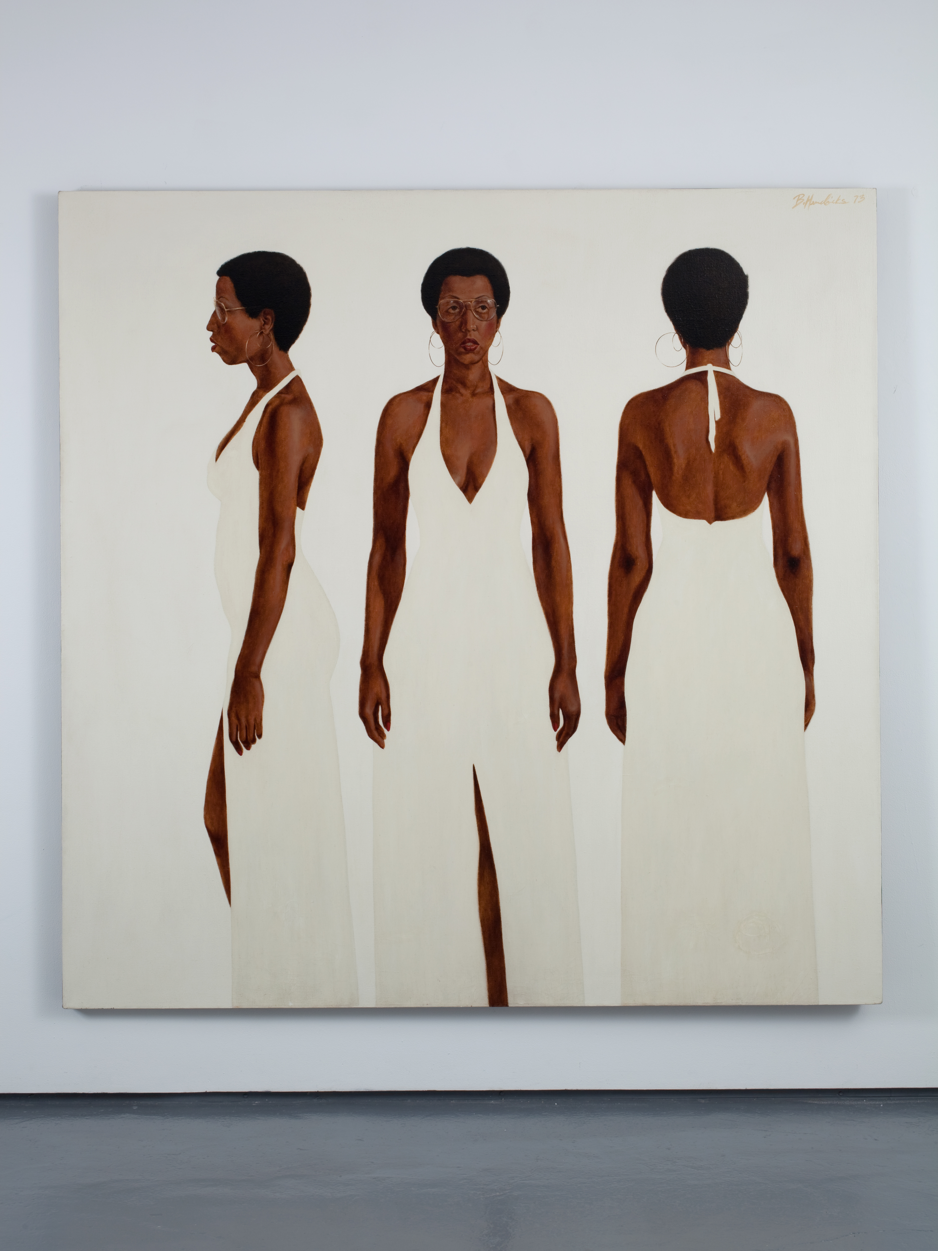 This photograph of a gallery shows a painting that depicts three different full-length views of a Black woman standing with her arms relaxed at her side. She wears hoop earrings, wire-rimmed glasses, and a long, white gown with a slit and a halter neck. Positioned against a matte white background, she stands as if seen, from left to right, in profile, from the front, and from behind.