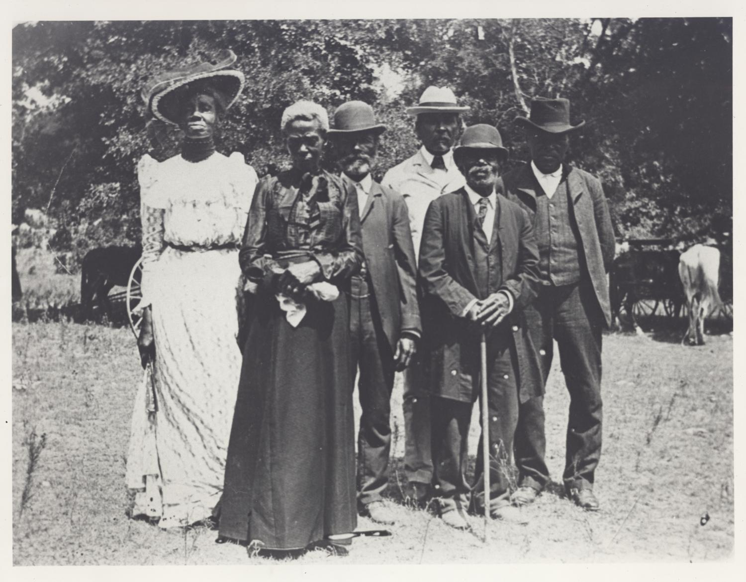 A black and white photograph portrays six Black individuals outdoors standing near one another and facing the camera. Two women at left wear long dresses; four men at right wear suits and hats. Partly visible behind them are carriages and a horse and trees.