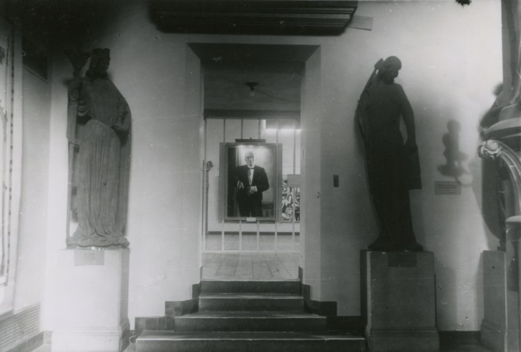 A black and white photograph shows four steps leading to a doorway into a gallery that frames the view of a painting of a man wearing a tuxedo and holding a cigarette. The doorway is flanked by full-length plaster cast sculptures of human figures atop large rectangular pedestals.