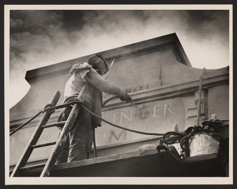 At an angular view from below, this black and white photograph depicts a man atop scaffolding using a tool to engrave letters into an entablature.