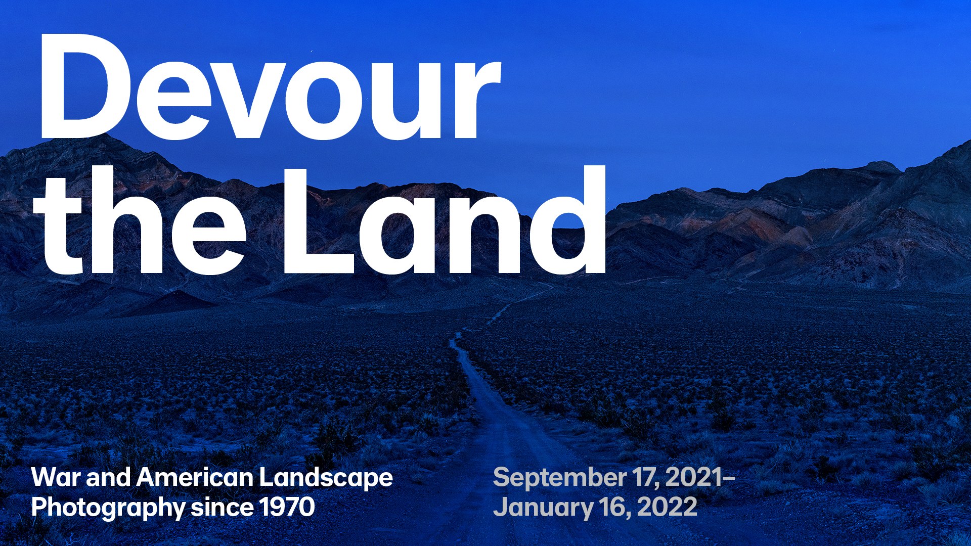 """A blue-saturated photograph of a desert landscape at night with a winding road in the foreground and mountains in the background. A blue-saturated photograph of a desert landscape at night with a winding road in the foreground and mountains in the background. In large white letters at the top are the words """"Devour the Land"""" and text at the bottom reads """"War and American Landscape Photography since 1970"""" and """"September 17, 2021–¬January 16, 2022."""""""