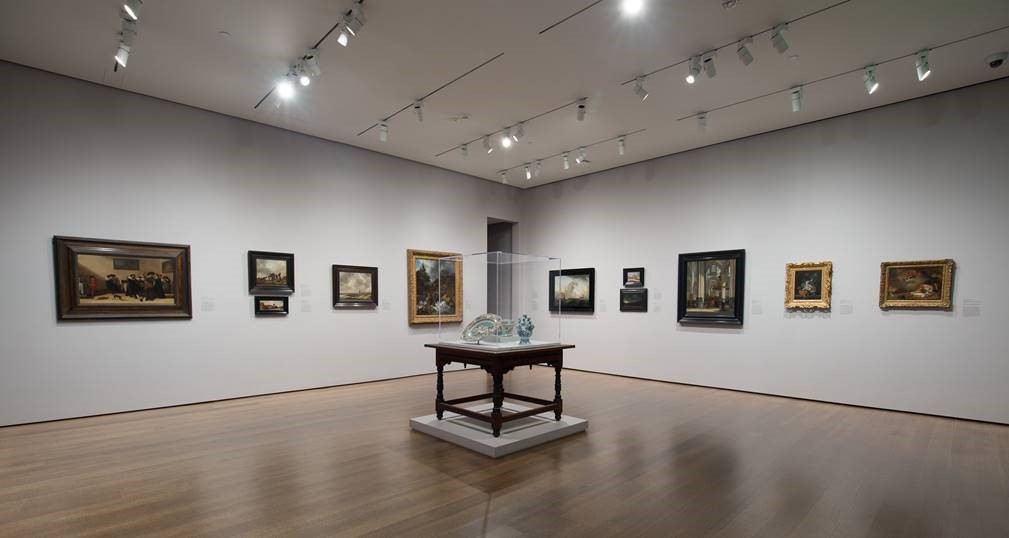 This installation shot shows part of a gallery with light gray walls and a brown wood floor. On the two visible walls hang eleven framed paintings. In the center of the floor stands a square-shaped wooden table; atop it are three porcelain objects within a vitrine.