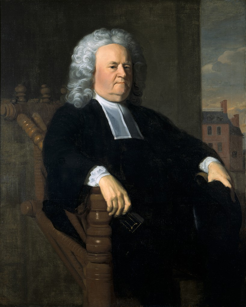 A light-skinned older man wearing a black robe sits in three-quarter profile on a dark wooden chair. White cloth sleeves appear at his wrists under his robe and a white, sheer, rectangular collar appears beneath his chin. His powdered peruke flows down to his shoulders. The wooden chair has many turned carvings and decorative elements. In the background is a multi-story brick building with a black roof.