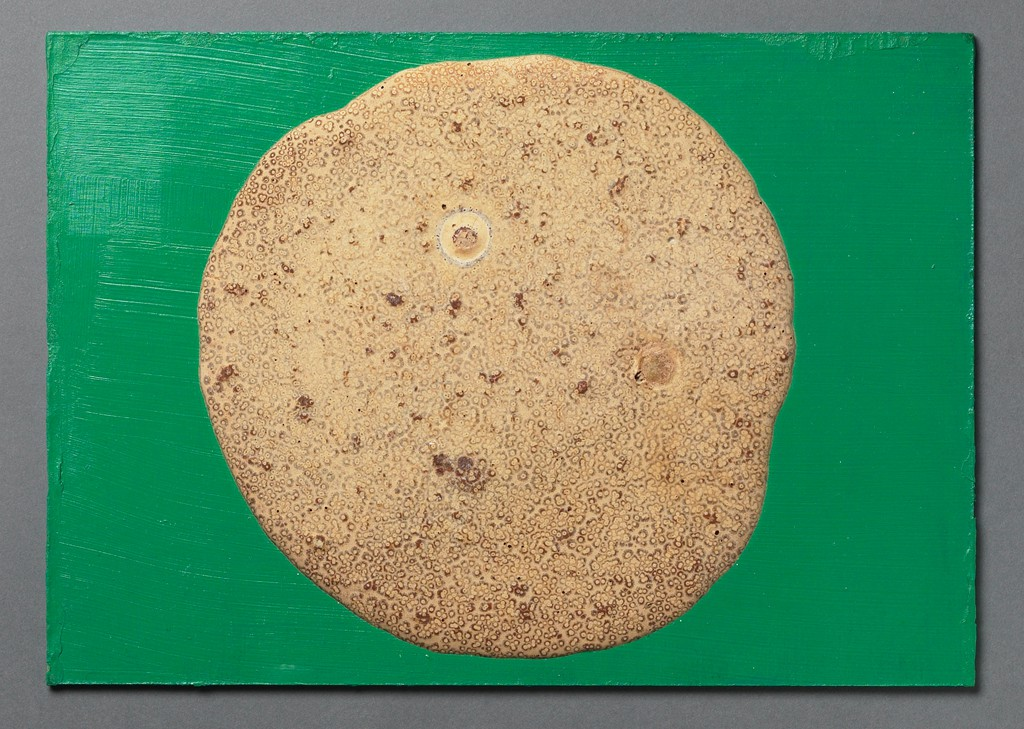 A light brown circular form consisting of pressed chocolate is centered on top of a wooden board painted bright green.