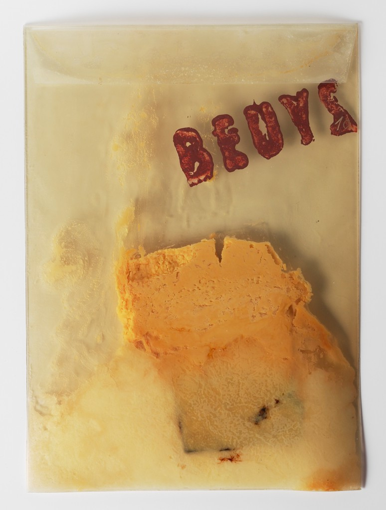 """A transparent PVC mailer stamped with the name """"BEUYS"""" in brown paint contains smeared margarine and part of a bar of white chocolate. It seems that some of the margarine is outside the mailer."""
