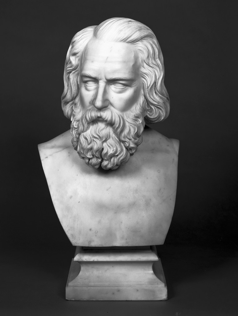 A white marble sculpture depicts a man's head and shoulders, mounted upon a marble pedestal. The man's nose is long and straight, and two wrinkles can be seen between his brows, which appear furrowed. The man's hair in parted on the right, combed back from his forehead and falling in waves just below his ears; a large, curly mustache and beard obscures the bottom-half of his face.