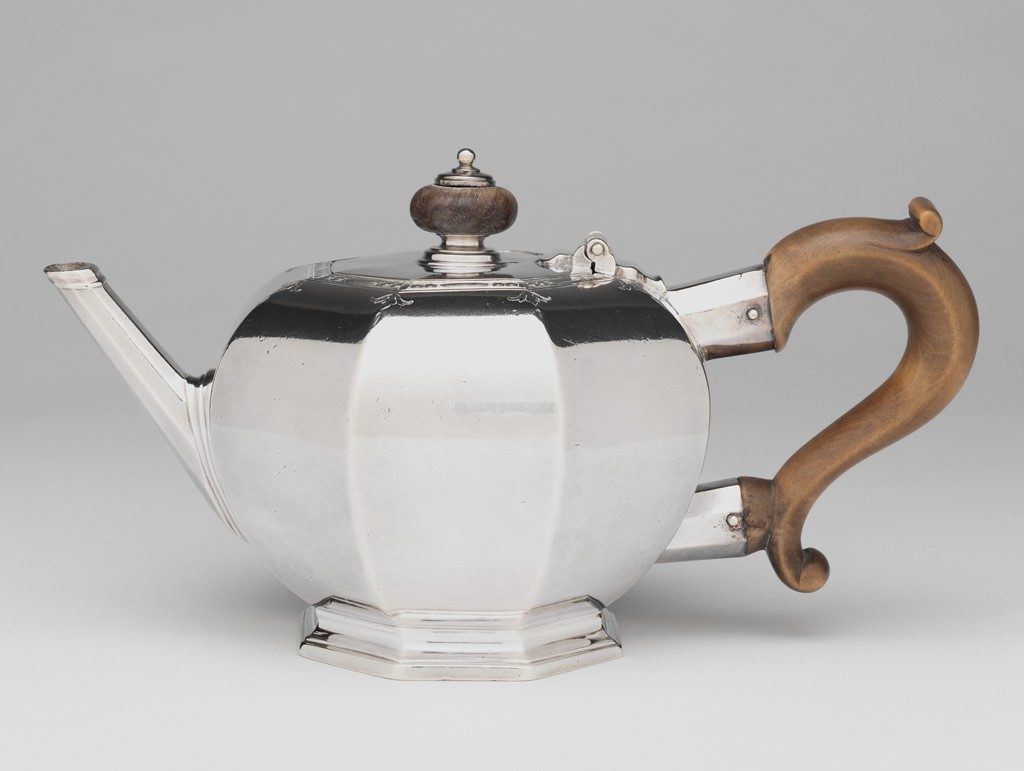 A silver teapot with a wooden handle and finial is shown from the side. Its spout is on the left and its handle on the right. The vessel body has three sections.