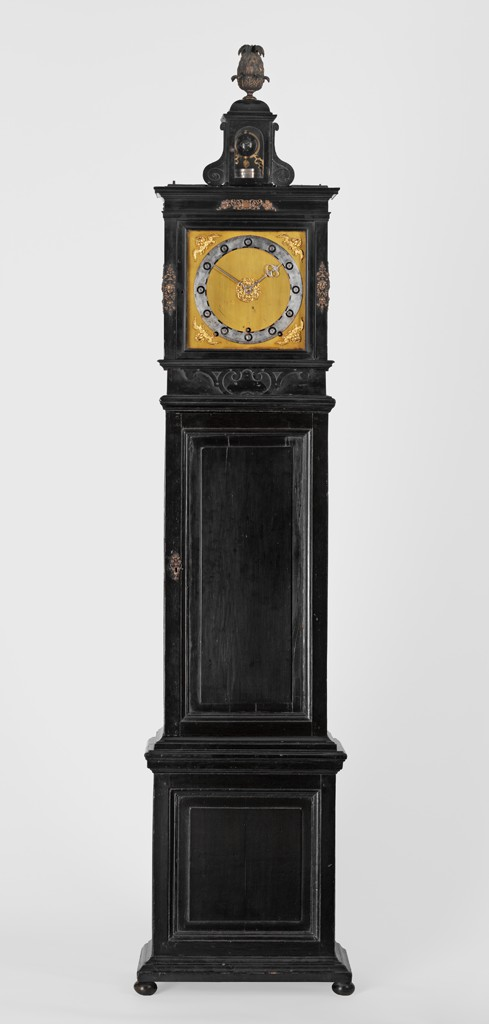 A square gilded clock face with hours inscribed on a silver circle is set in a tall, tripartite wooden cabinet.