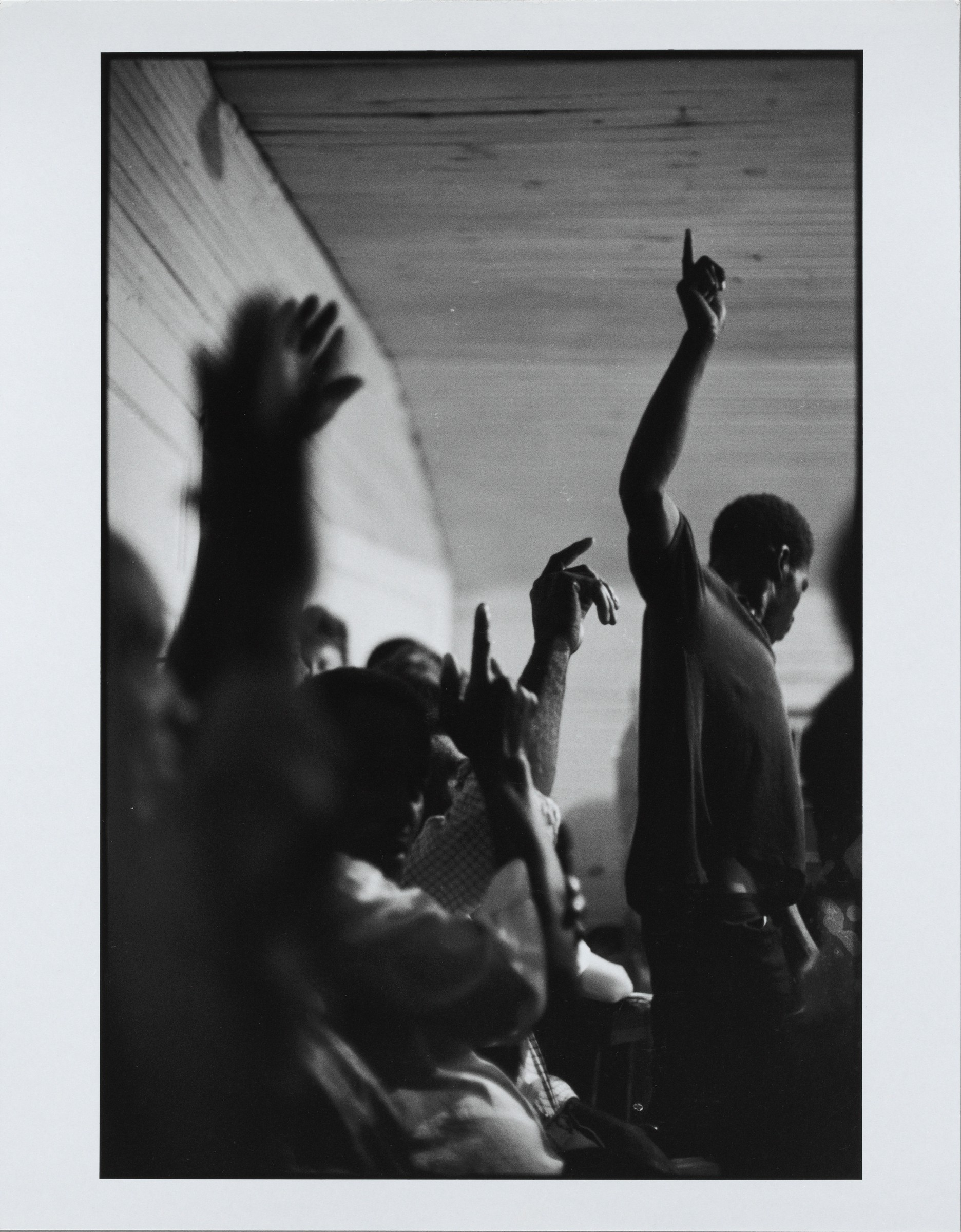 This black and white photograph captures a crowd of Black men and women in a room. To the right, a tall man in dark clothing raises his right arm, with his index finger pointing up. More people appear on the left; it is hard to make out details, but several raise their arms. The figure at the left edge of the image is blurry.