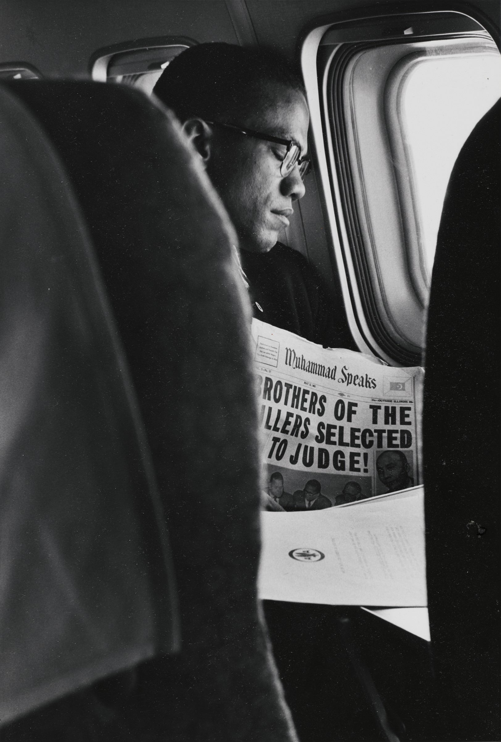 """This black and white photograph presents a view between airplane seats of a Black man with his eyes closed, glasses on, and resting his head against a luminous window. The headline of the Muhammad Speaks newspaper on his chest reads (with some letters not shown) """"Brothers of the killers selected to judge!"""""""