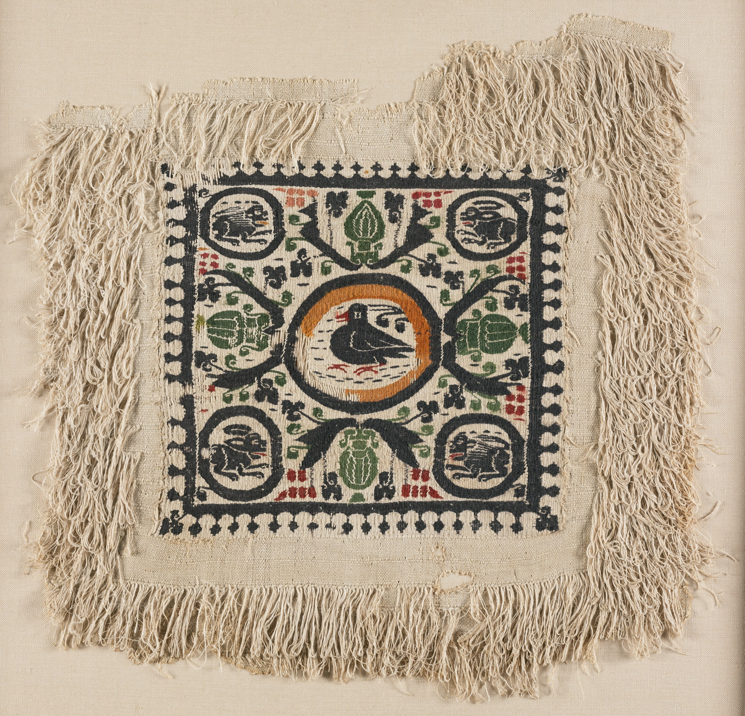 A square piece of beige cloth with looped threads has a smooth inner square with colorful designs. In a central roundel sits a plump bird and in each corner a rabbit or lion. The remainder of the inner square is decorated with four green urns and dark-colored vines with red and pink grapes.