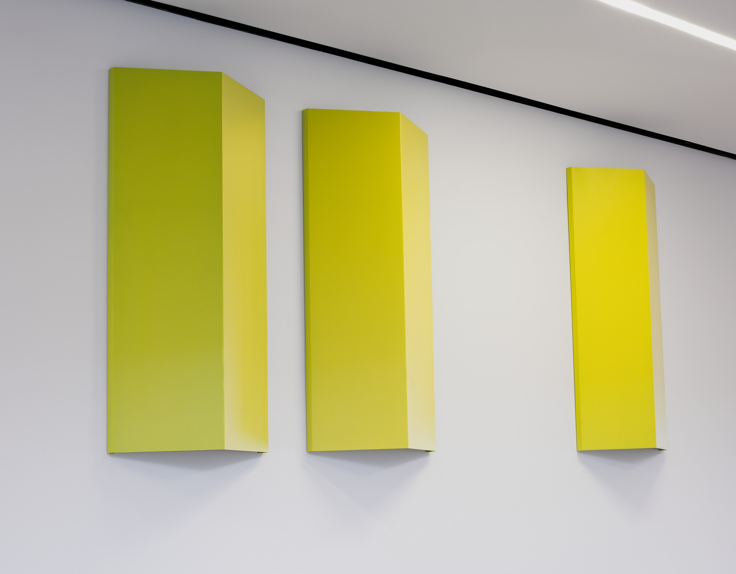 Three identical, yellow-painted aluminum sheets, each folded convexly, are mounted in a vertical orientation and parallel to each other on a white wall.