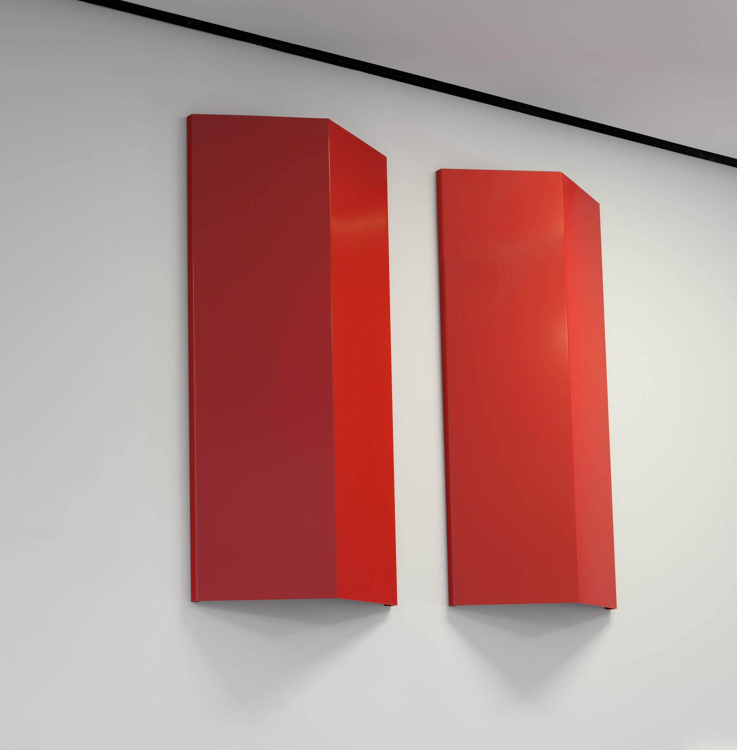 Two identical, red-painted aluminum sheets, each folded convexly, are mounted in a vertical orientation and parallel to each other on a white wall.