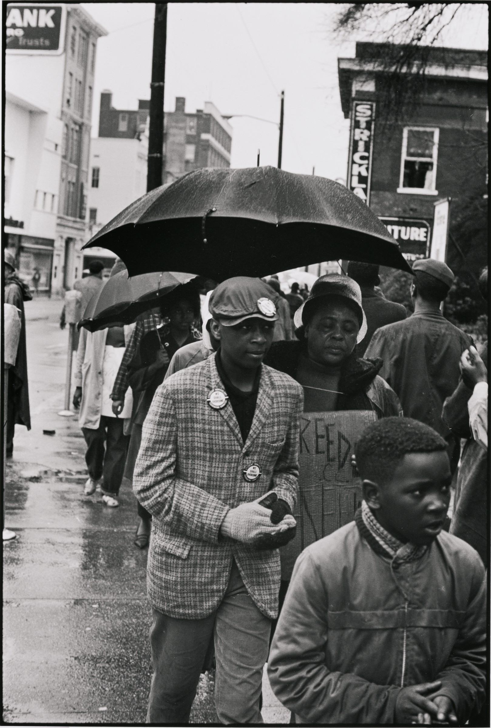 "This black and white photograph shows Fannie Lou Hamer marching under a black umbrella in a wet street accompanied by a group of young Black Americans. The young man marching next to Hamer has three buttons pinned on his clothes and hat that read ""We Shall Overcome."" A boy in the foreground clasps his hands. Brick buildings on both sides of the street are visible in the background."