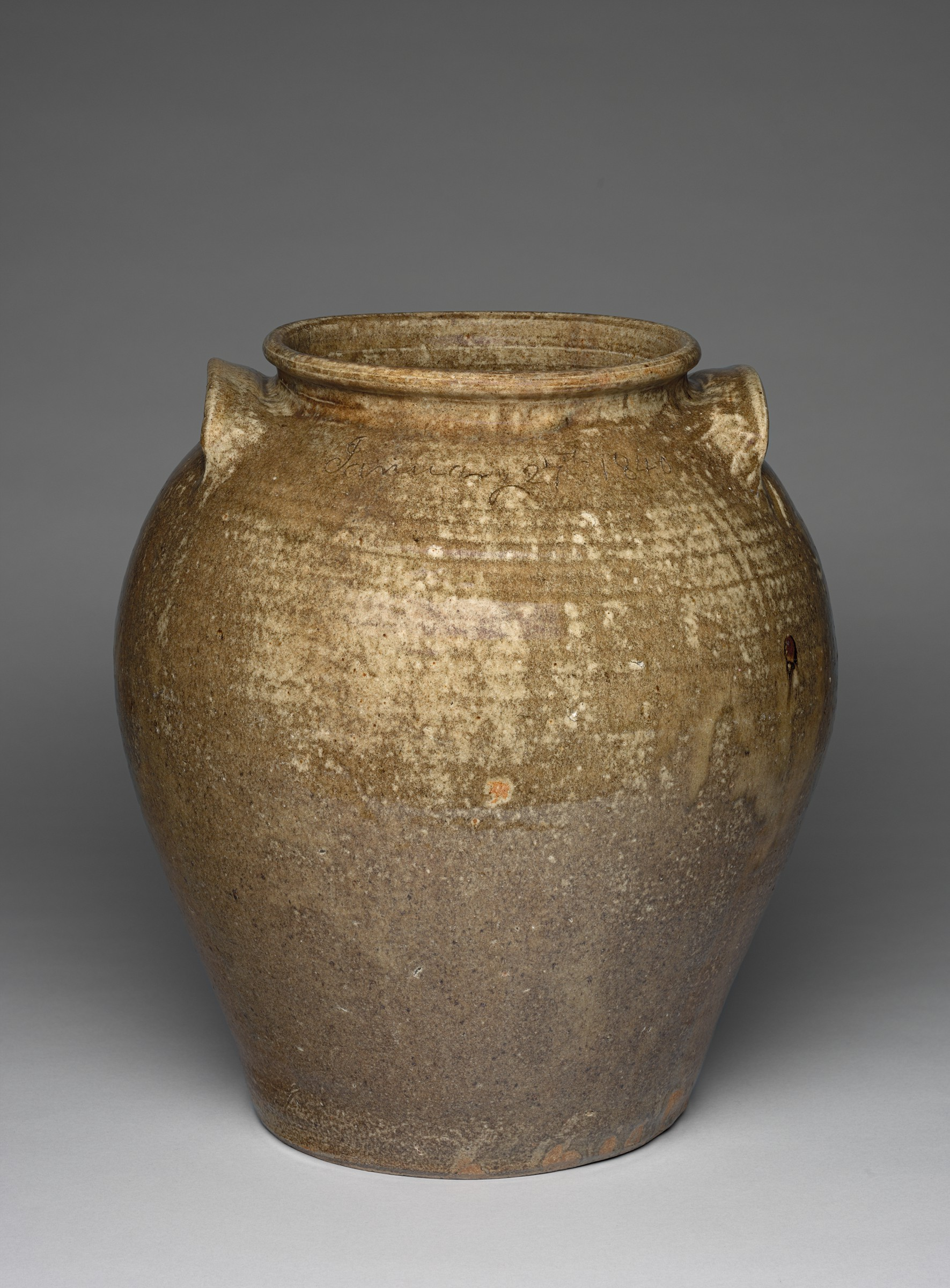 This brown and  tan ceramic jar has two handles and is shown against a gray background. The surface is worn in many places and chipped in others, revealing  the reddish hue of the clay  and horizontal striations.  The mouth and base are approximately the same diameter, while the body of the jug  is broader.