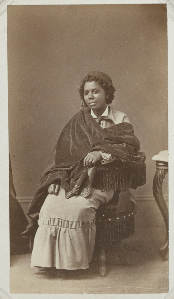 A black and white photograph shows a medium-dark skinned woman seated on a fringed chair. With one hand resting on the arm of the chair and the other lying on her knee, Lewis's soft gaze extends beyond the picture plane. A dark, heavy velvet cloak with a geometric border is draped across her arm and shoulder; she wears a light-colored dress with a ruffled hem, a white collar, and a necktie. A fez-like hat with a tassel is perched upon her dark hair, which is arranged in waves that frame her face. An ornate, curved leg of a chair or table can be seen on the right-hand side of the picture plane.