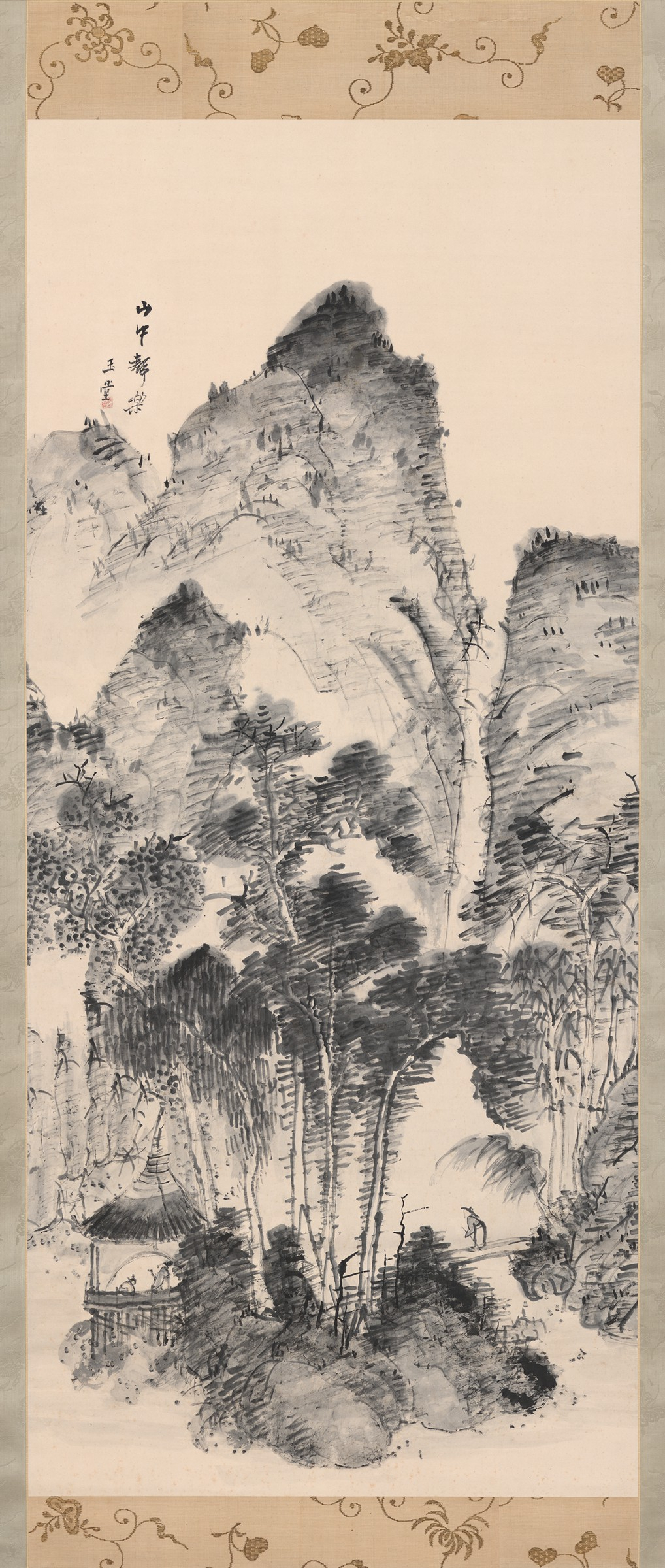 This vertical hanging scroll renders a mountainous landscape in monochrome ink. Three trees occupy the central foreground, where a hatted figure crosses a bridge at right to reach two figures in a thatched pavilion at left.