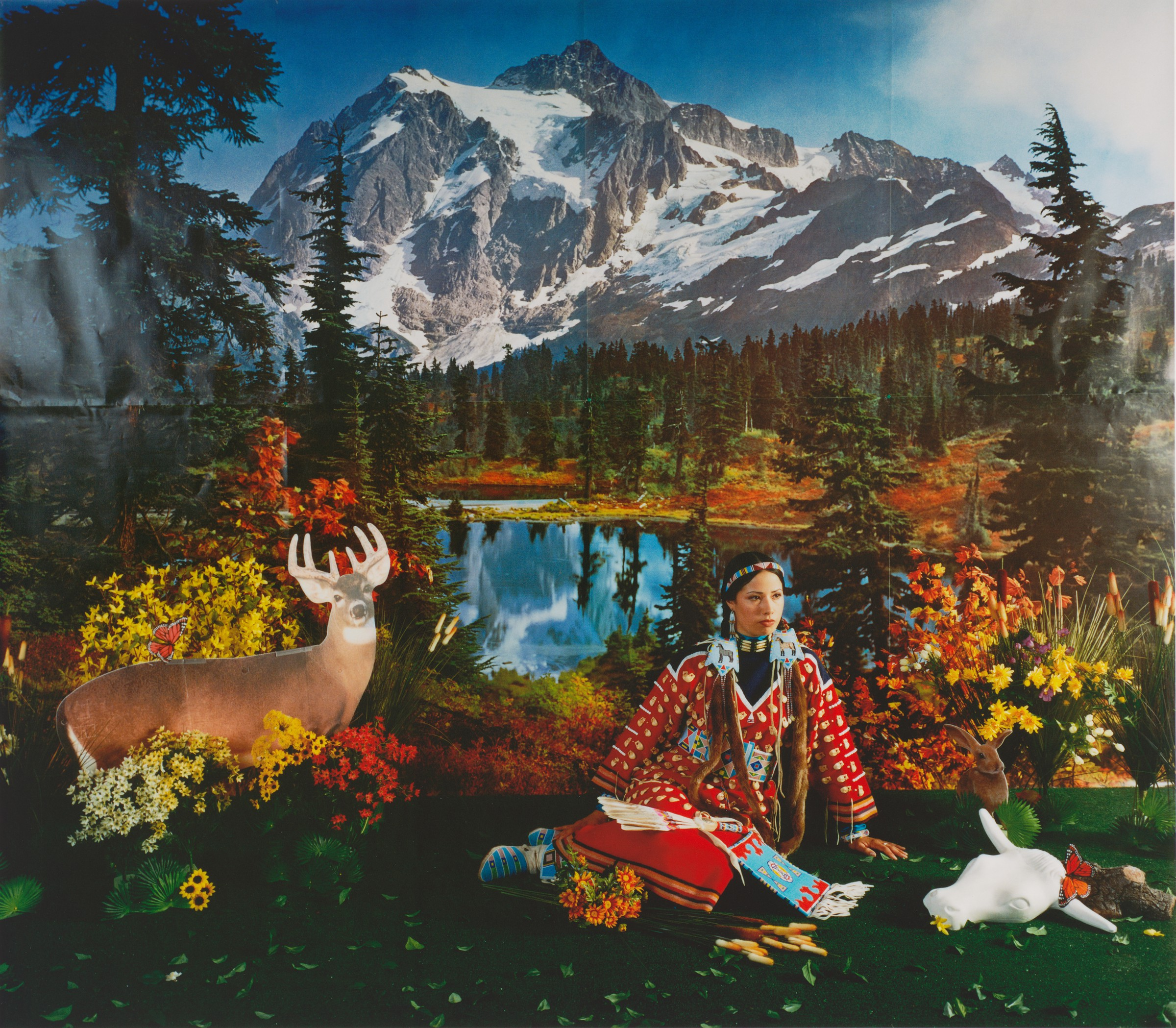 A color photograph of a landscape with snowcapped mountains, coniferous forests, and a lake. In the foreground, a Native American woman in traditional dress kneels on the ground surrounded by various artificial and real animals, shrubs, and flowers.