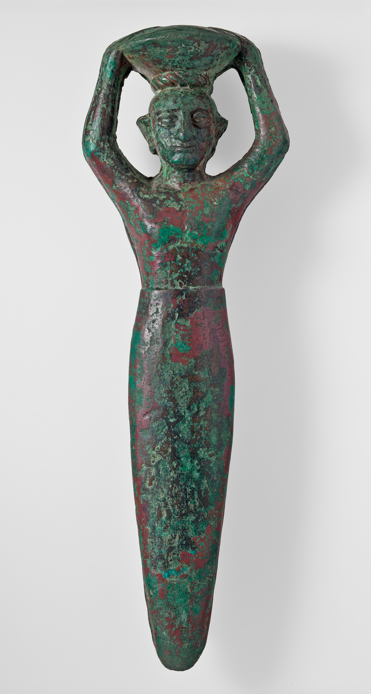 This copper figure carries a shallow basket on its head; both arms are raised to support the basket. The beardless man's upper body is naked, and the lower body takes the shape of a slightly flattened peg. The surface of the object is dark brown, with extensive patches of light green and dark red corrosion.