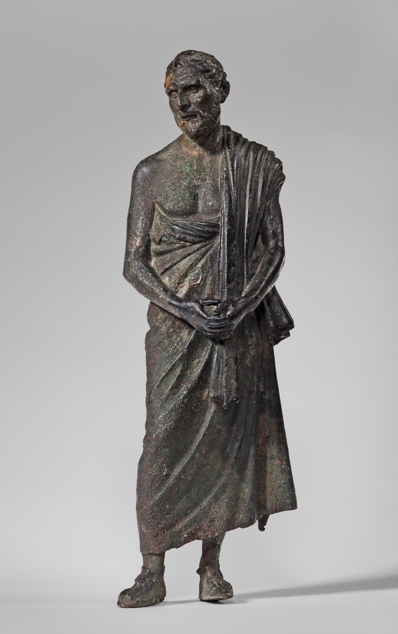 A dark brownish-green statuette depicts a man standing with his hands clasped in front. His right shoulder is bare, and a cloth garment is pulled around his torso and draped over his left shoulder. His head is cocked slightly to his right, and he is bearded.