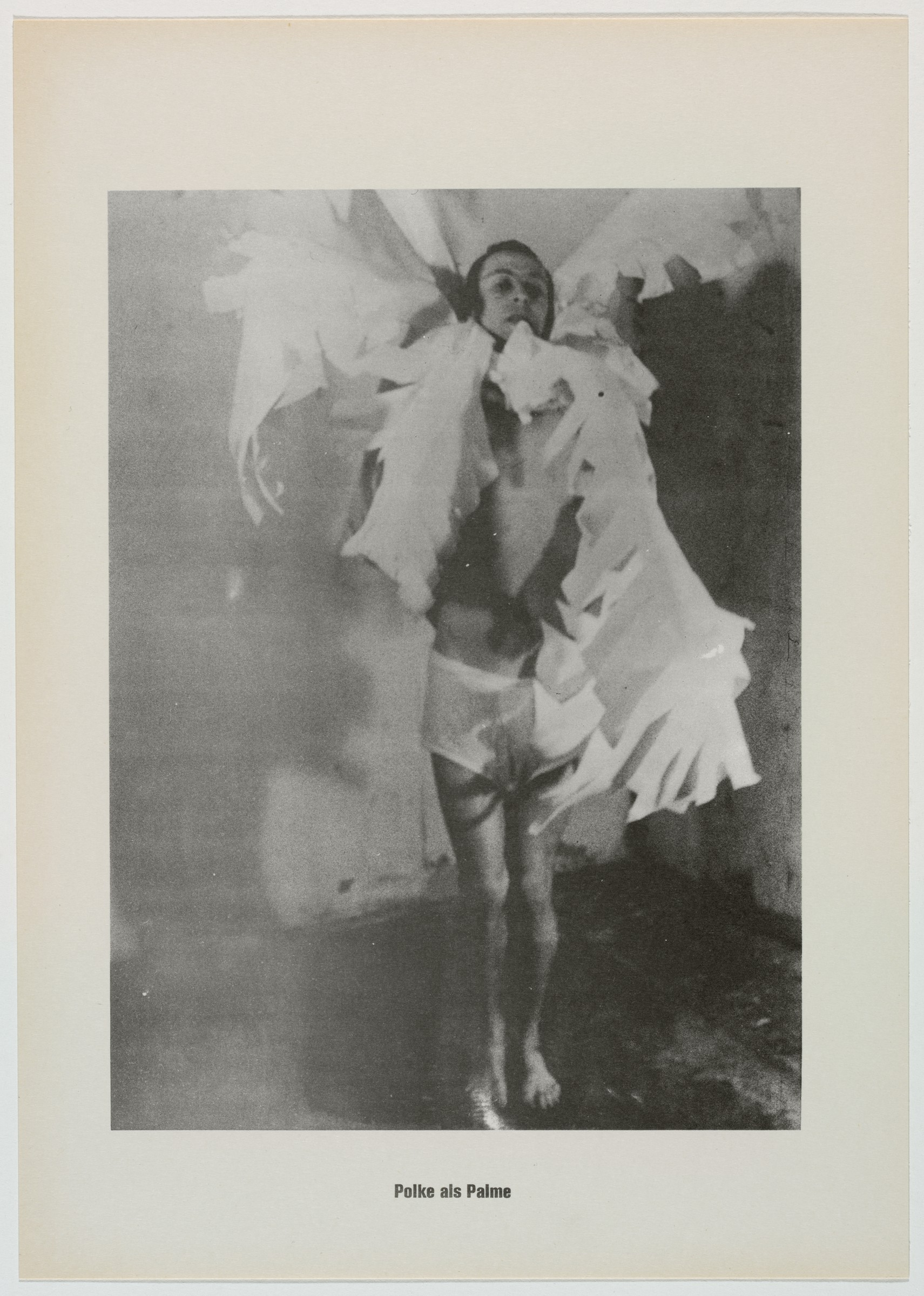 """This black and white lithograph shows a man with dark hair standing in a room barefoot on a dark floor with lighter walls behind and to the right. His head is slightly raised, and he is wearing white shorts with large cutouts of palm fronds around his neck. Text at the bottom reads """"Polke als Palme."""""""