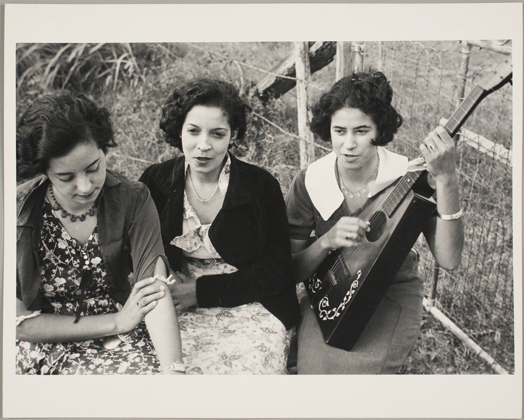This black and white photograph shows three young women in summer dresses sitting next to a fence, with grass behind and to the right of them. The woman at far right is playing a triangular ukulele.