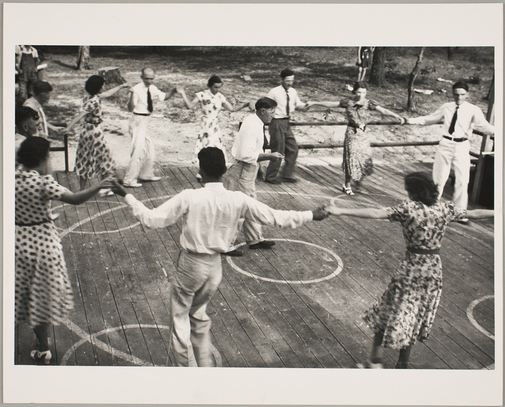 This black and white photograph shows a group of women and men on a dance floor situated in a natural setting. The group is forming a wide circle with alternating female and male participants and holding hands, as they dance around a man in the center, presumably the teacher. Women are wearing short-sleeved, long summer dresses, and men wear light pants, white shirts, and ties.