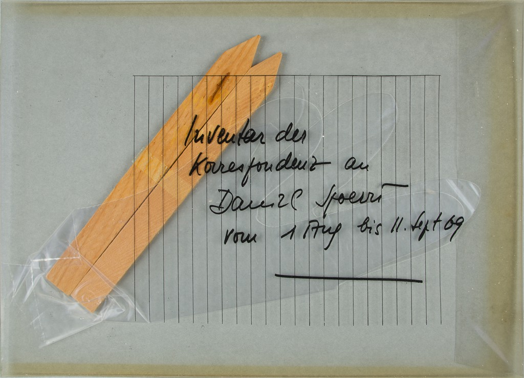 A transparent PVC mailer with a handwritten inscription in German contains a plastic glove, two orange wooden sticks, and the surface of a lined piece of paper.