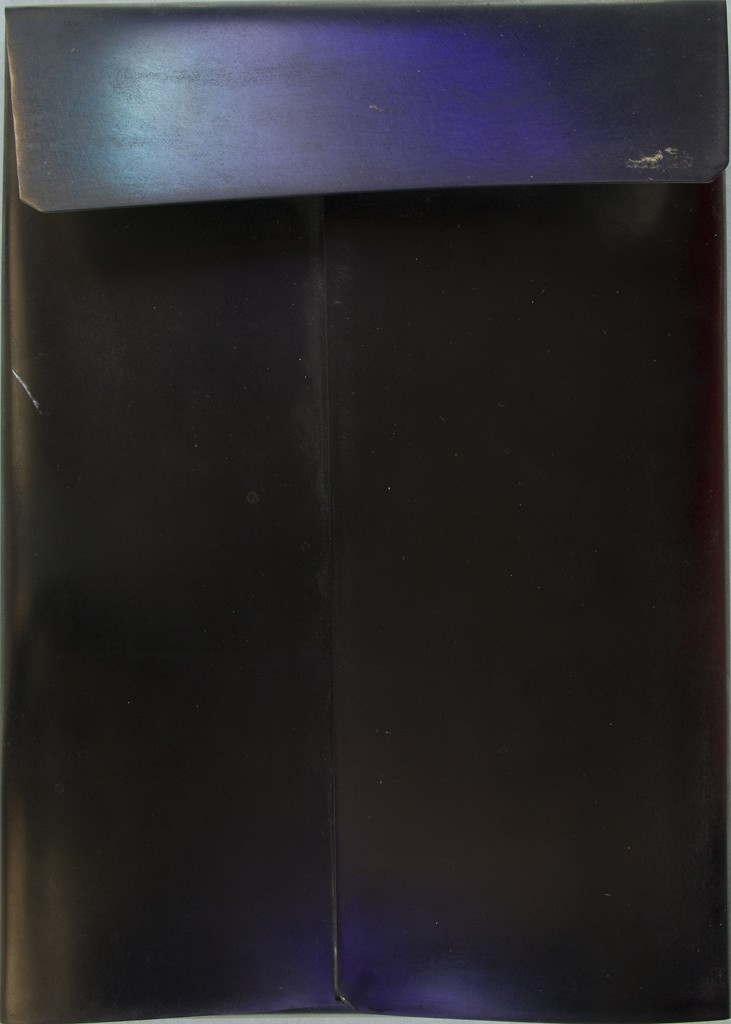 """A piece of stainless-steel sheet metal is folded into the shape of a postal mailer. The upper """"flap"""" reflects a bluish-purple light."""