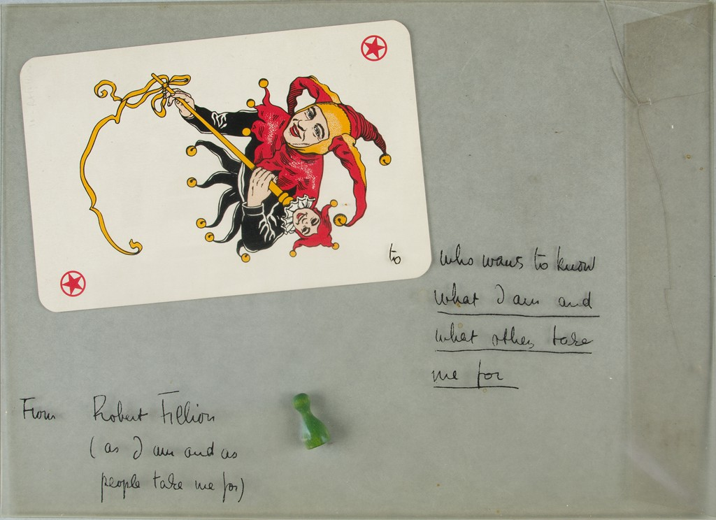 """A transparent PVC mailer shows the text """"From Robert Filliou (as I am and as people take me for"""" at bottom left. On the right side of the envelope, the text reads: """"who wants to know what I am and what others take me for."""" An oversized playing card, which shows a joker dressed in red and black, and a plastic green game piece rest on top."""