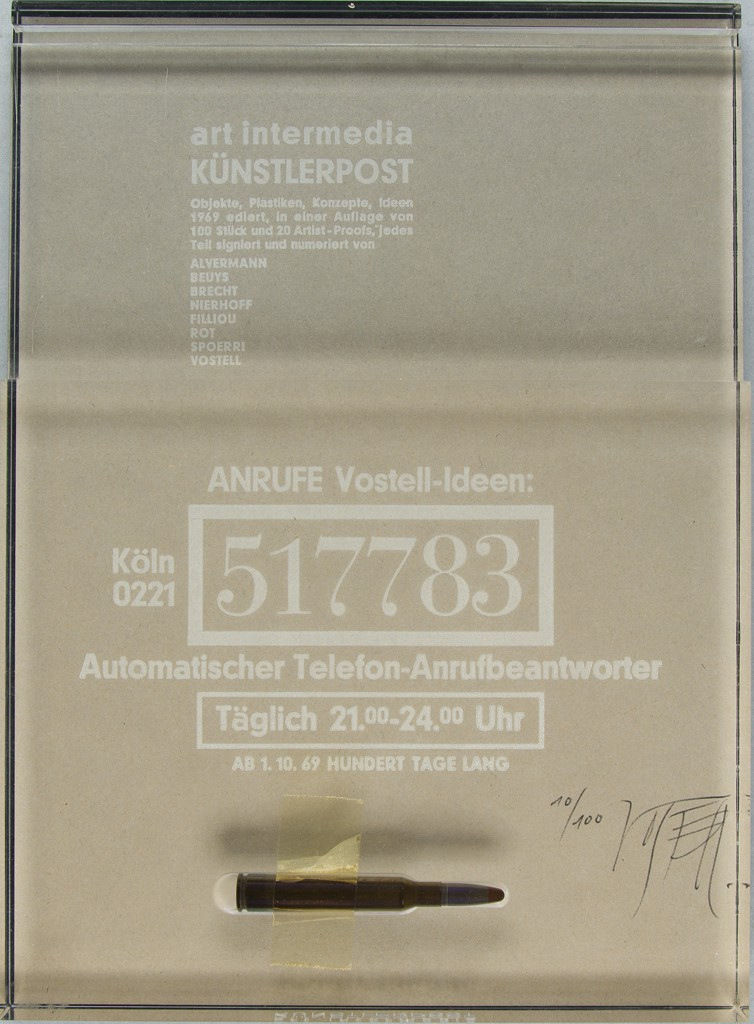 """A transparent Plexiglas blotter shows printed white text in German and the number """"517783"""" at center. A beige blind-embossed card is beneath the surface. A recess at the bottom of the blotter is fitted with an empty rifle cartridge."""