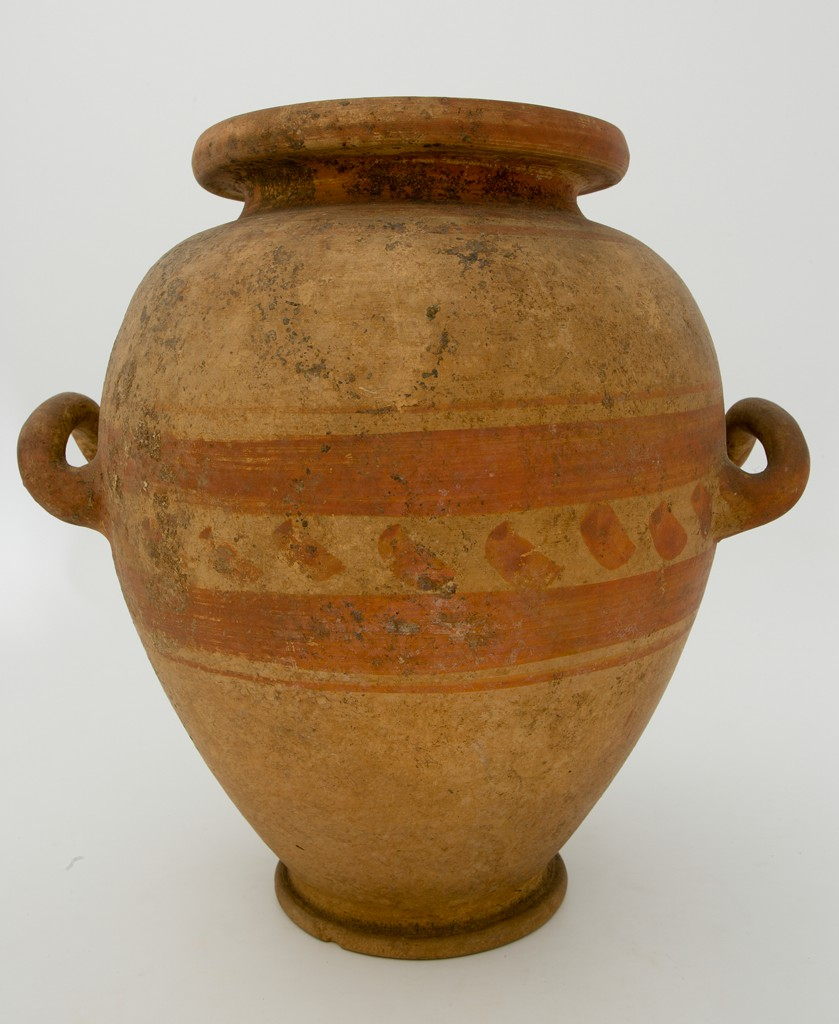 An egg-shaped terracotta jar tapering toward a ring foot, its wide mouth surrounded by an offset rim. Below the shoulder, a little more than halfway up the vessel, sit two horizontal, upward-curving handles. The jar is light brown, with darker areas of dirt on its surface. Between the two handles extends a zone of reddish-brown painted decoration consisting of diagonally applied brushstrokes framed above and below by a broad band and a single line. A painted line also encircles the vessel rim.