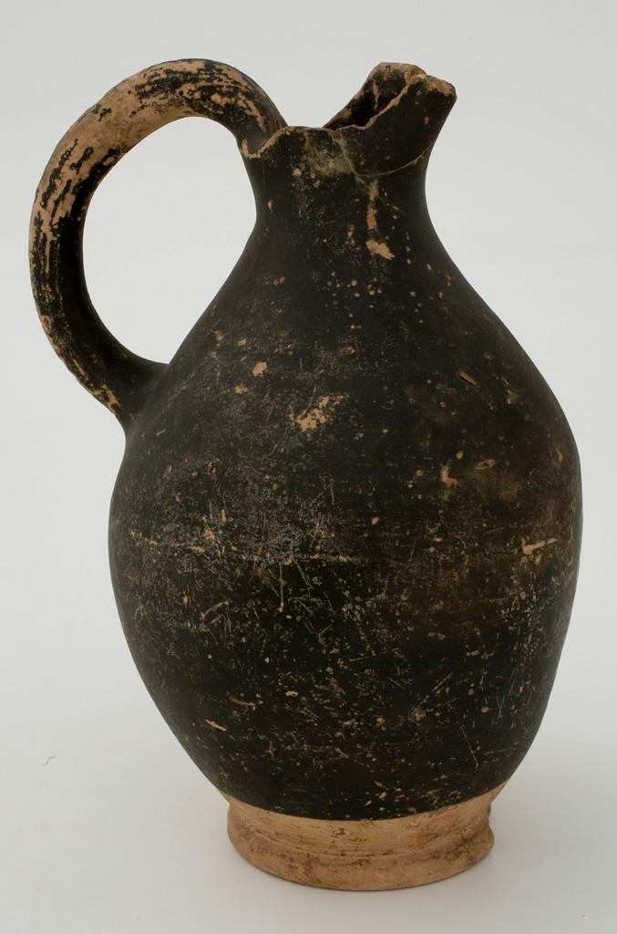 This photograph shows a black pitcher with a continuous curve from rim to ring foot and a prominent handle jutting out on one side. On the other side of a narrow neck is the upward-pointing spout, whose edge is partly missing. The small base is light brown.
