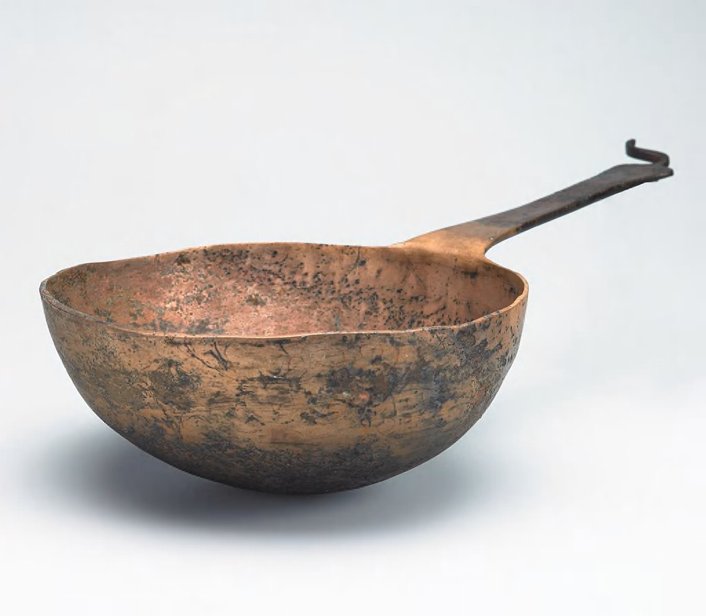 This photograph shows a reddish-gold metal dish of rounded, almost hemispherical shape with a long, flat handle that ends in a curved appendage. The dish has dark brown areas throughout, including most of the handle. The walls of the vessel are uneven, and hammer marks are visible in its surface.