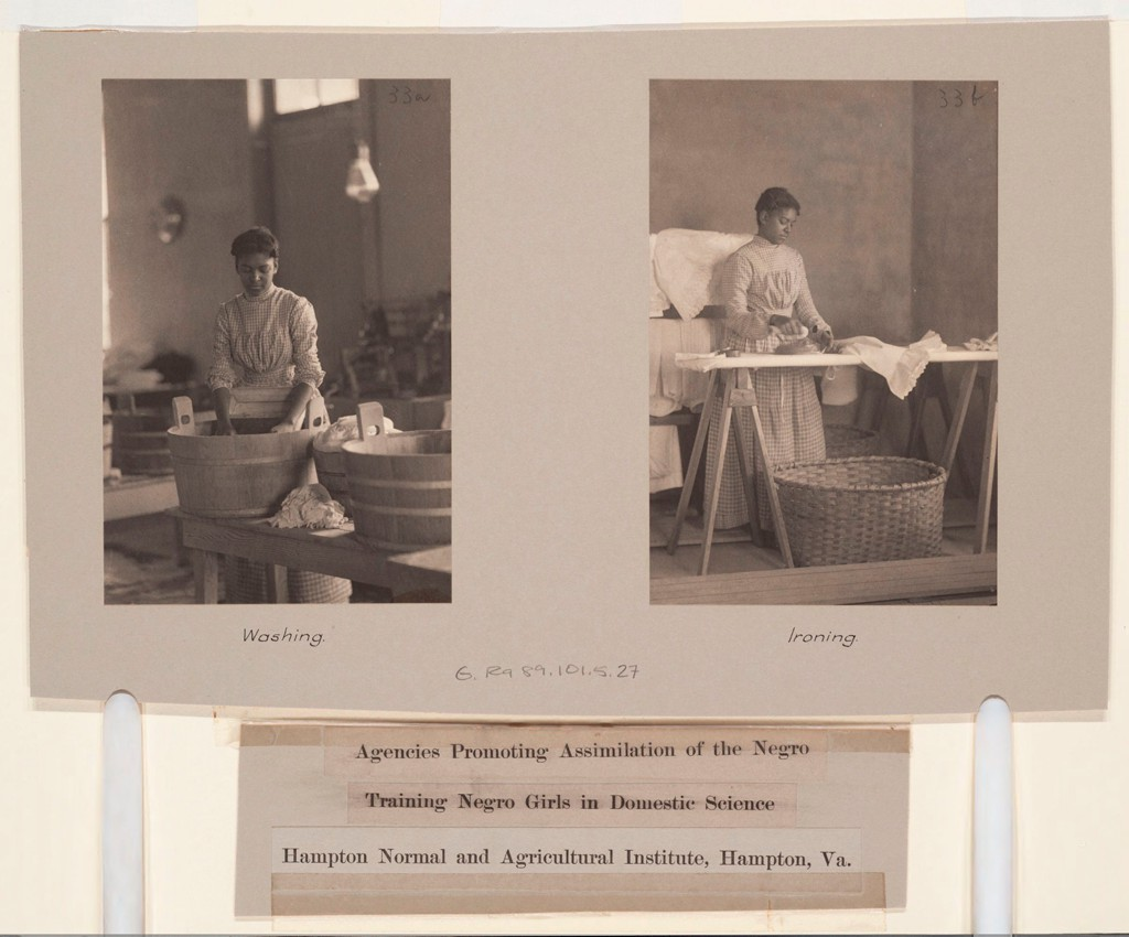 "Pasted onto a yellow board is a gray paper with two side by side black and white photographs. The one at left shows an African American woman in front of a wash basin. The caption reads ""Washing."" At right is an image of an African American woman ironing a white cloth on a standing board. A large wicker basket is on the floor in front of the board. The caption reads ""Ironing."" Below the gray paper are the typewritten words ""Agencies Promoting Assimilation of the Negro. Training Negro Girls in Domestic Science. Hampton Normal and Agricultural Institute, Hampton, Va."""