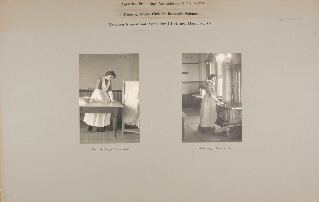 "Pasted onto gray paper are two side by side black and white photographs. The one at left shows an African American woman cleaning a table. She wears a white apron. The caption reads ""Scrubbing the Table."" A drying rack to the right holds white sheets. The photograph at right shows an African American woman wearing an apron. She is rubbing a cloth over the top of an iron stove. The caption reads ""Polishing the Stove."" Typewritten text at top of both images reads ""Hampton Normal and Agricultural Institute, Hampton, Va."""