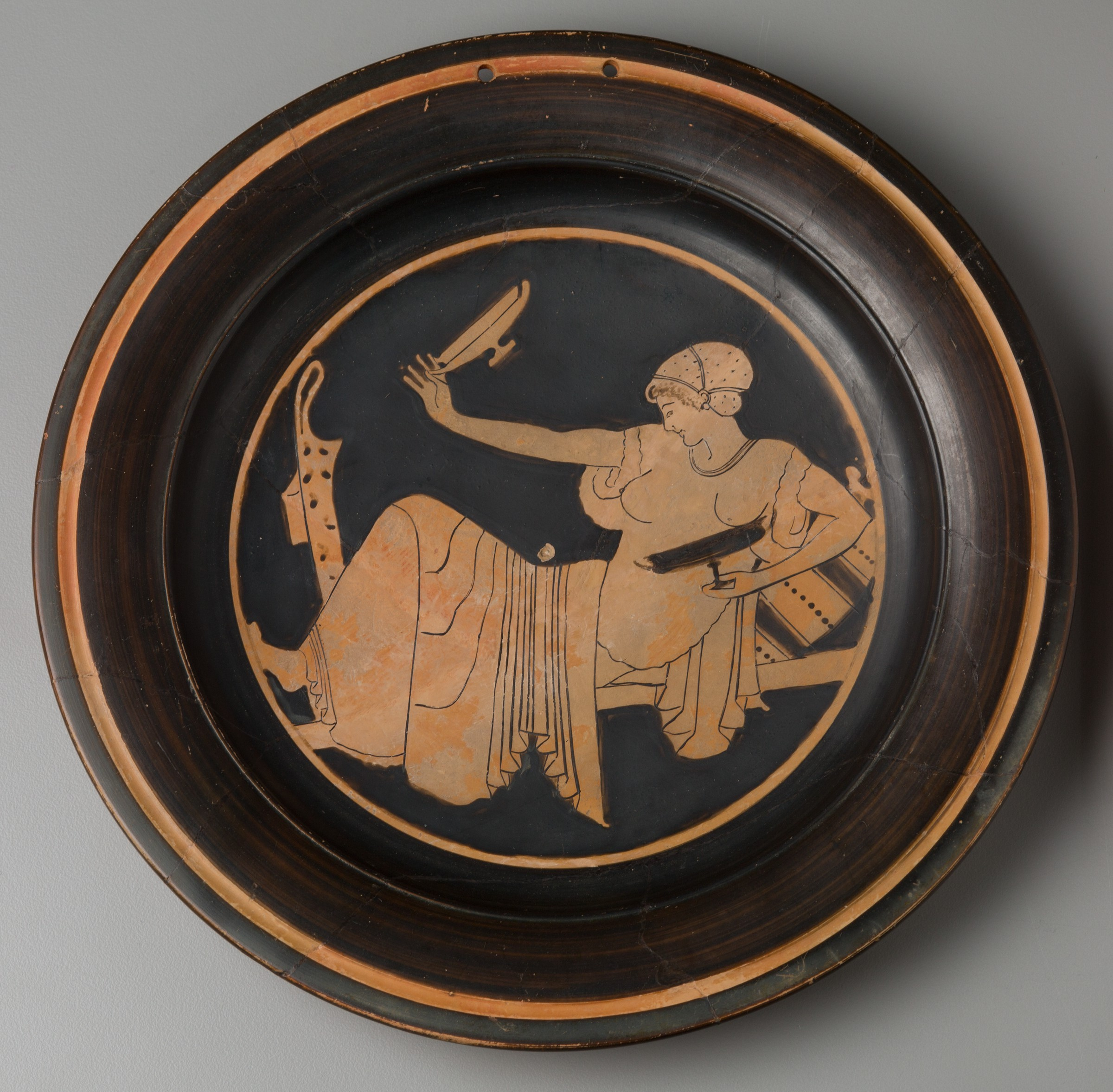 The center of this round plate depicts a woman reclining on a horizontal surface, facing left. She appears in a light reddish-brown clay color, while the background is glossy black. Her knees are bent, and her upper body is propped up on a decorated pillow. Her clothing is draped in elaborate folds. With her left hand, she holds a shallow, stemmed cup rendered in black silhouette in front of her body. A second, clay-colored cup of the same shape is held aloft in her right hand.