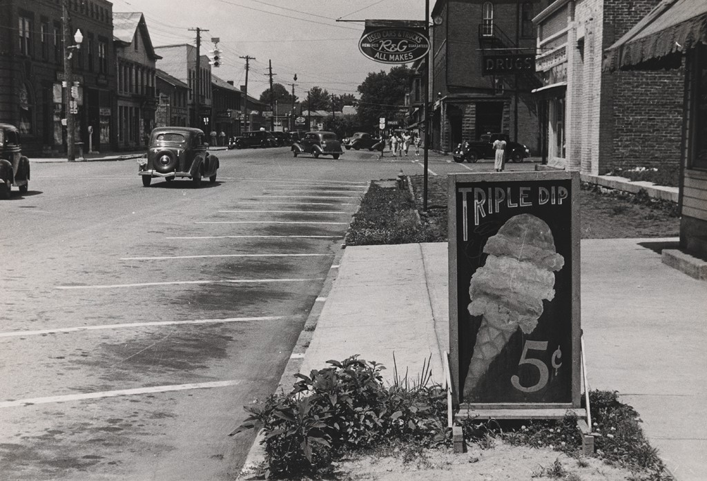 """The black and white photograph shows sparse car traffic on a small town street, with lots of empty parking spaces and a deserted sidewalk. In the foreground at right, a hand-painted sign on the sidewalk shows an ice cream cone topped with three generous scoops. The text above the ice cream cone reads """"Triple Dip"""" and below it """"5¢."""""""