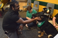 Vamsi Vallurupalli learns about the dogs of the Monroe County Human Society from Lori Shields at the WonderLab on Sunday.