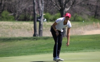 Freshman Emma Fisher picks her ball out of the hole after sinking a putt Saturday at the IU Invitational at the IU Golf Course. She was smiling at her mom, who was a spectator.