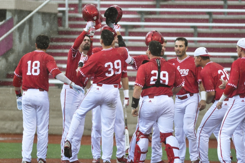 IU players meet senior outfielder Craig Dedelow at home plate after he hit a grand slam in the seventh inning of a game against Maryland on Sunday. IU won 6-3.