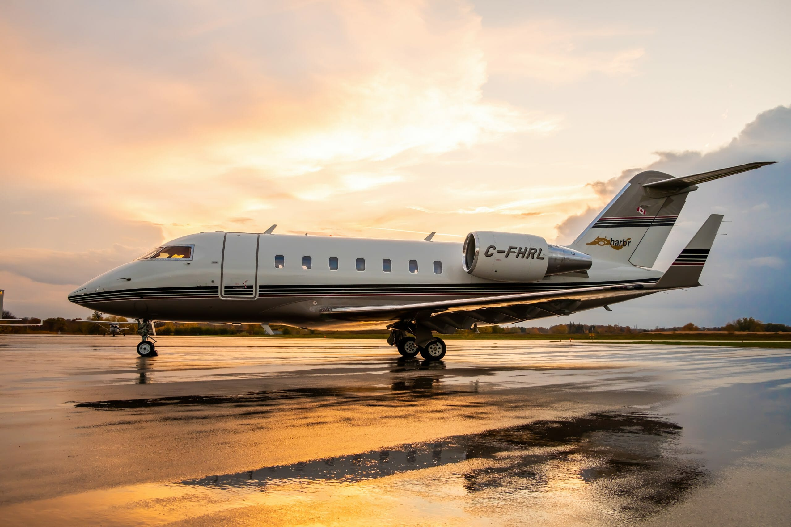 Private jet, grounded, in front of a sunset