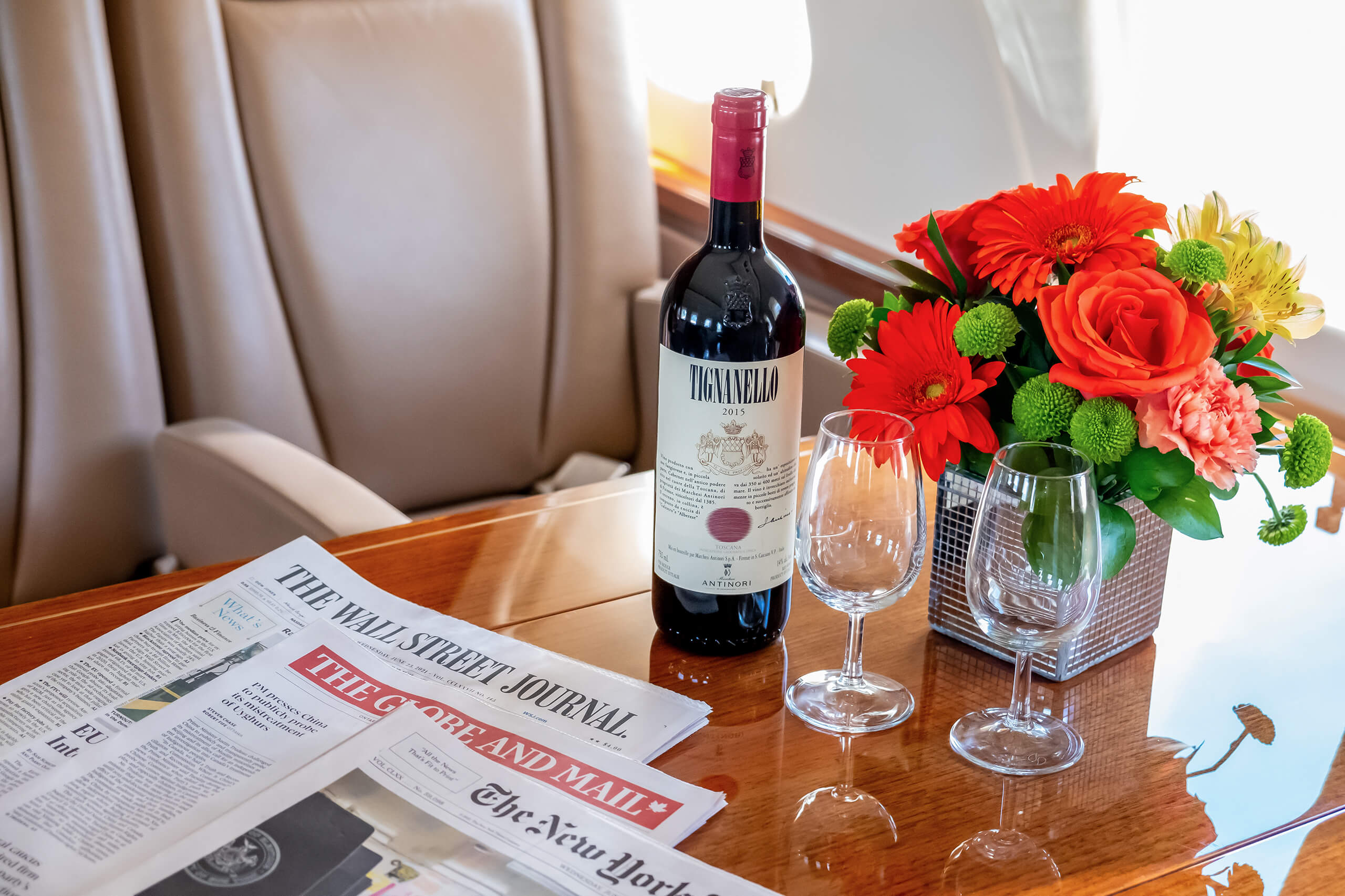 Red wine, wine glass, bouquet of flowers and newspaper on the table of a private jet.