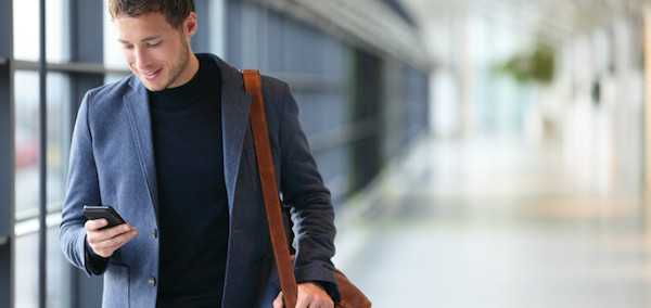 Man on smart phone - young business man in airport. Casual urban professional businessman using smar