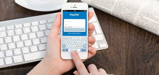 Female Hands Holding A White Iphone With Registration Paypal