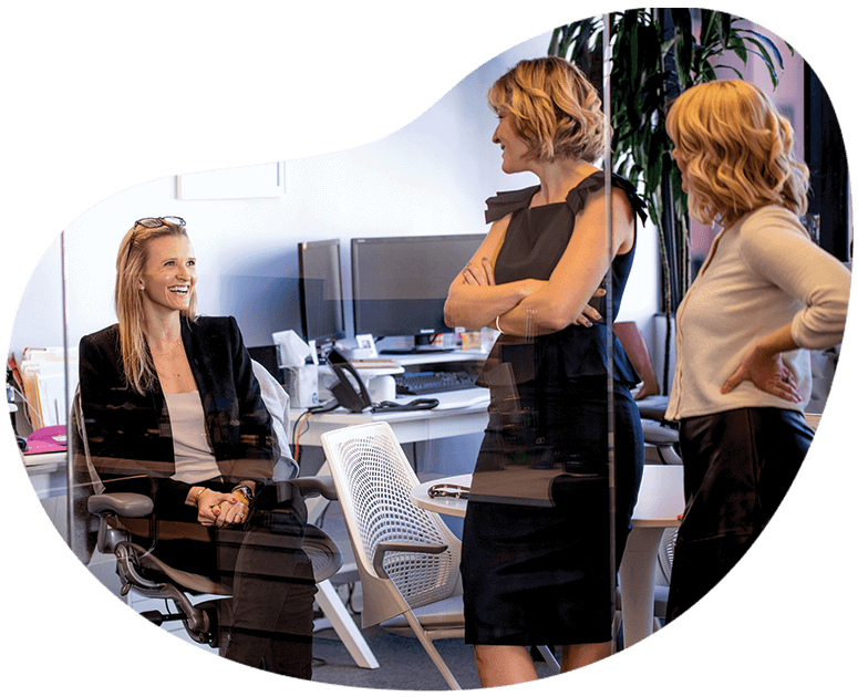 Three females discussing strategy around our franchise public relations firm